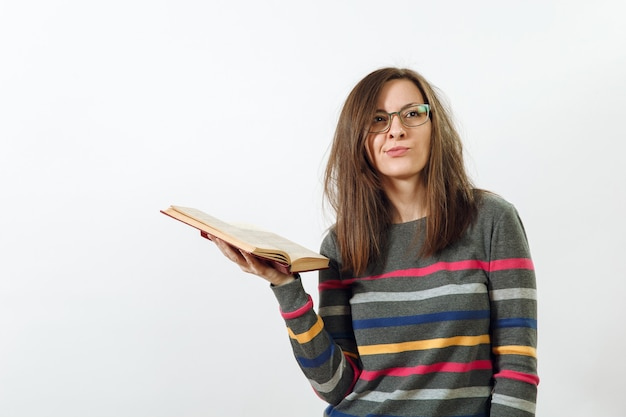 A beautiful european young brown-haired woman in glasses for sight dressed in casual dark grey longsleeve with colorful stripes, standing with book on a white background. reading and studying concept