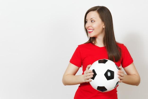 Красивая европейская молодая веселая счастливая женщина, футбольный фанат или игрок в красной форме, держащий классический футбольный мяч на белом фоне. спорт, играть в футбол, здоровье, концепция здорового образа жизни.