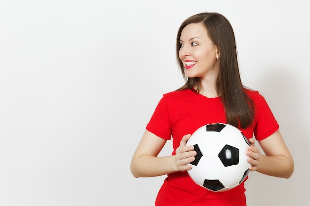 Beautiful european young cheerful happy woman, football fan or player in red uniform holding classic soccer ball isolated on white background. sport, play football, health, healthy lifestyle concept.