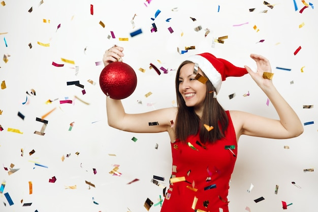 Beautiful european young happy woman with charming smile in red dress and christmas hat holding big tree toy on white background and confetti. santa girl isolated. new year holiday 2018 concept.
