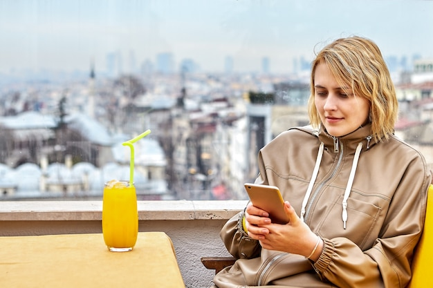 Beautiful european young woman in her 20s with glass of juice by window in cafe overlooking istanbul cityscape reads messages on smartphone screen.