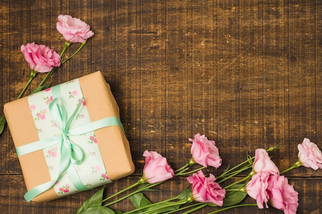 Beautiful eustoma flower and decorative wrapped present box over wooden textured