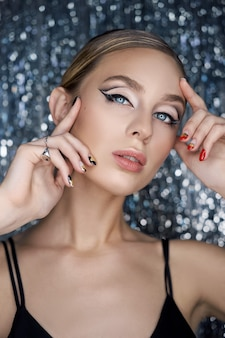 Beautiful evening eye makeup of a blonde woman on a shiny background. close-up portrait of a woman, perfect eye makeup, skin care