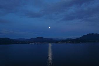 美しい夜の土地。湖と山の月の道