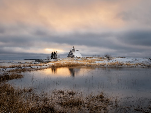 崖の上の夕暮れ時に小さな本物の木造住宅と美しい夜の冬の風景。ロシア。