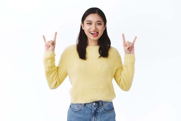 Beautiful excited asian girl having fun on awesome concert, making rock-n-roll gesture and showing tongue as smiling carefree, dancing to cool music, standing white wall
