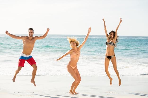 Красивые возбужденные друзья прыгают на пляже