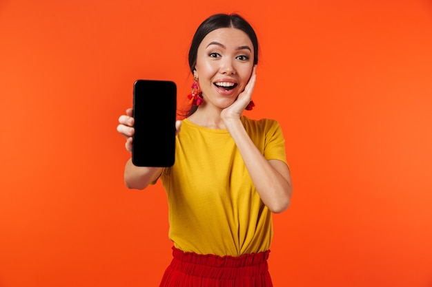 Beautiful excited happy young woman posing isolated over orange wall showing display of mobile phone.