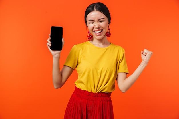 Красивая возбужденная счастливая молодая женщина позирует изолированной над оранжевой стеной, показывающей дисплей мобильного телефона.