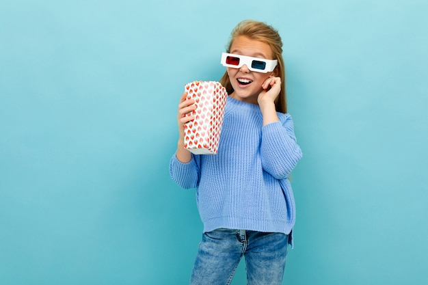 Beautiful excited schoolgirl with popcorn and glasses for 3d movie on a blue background