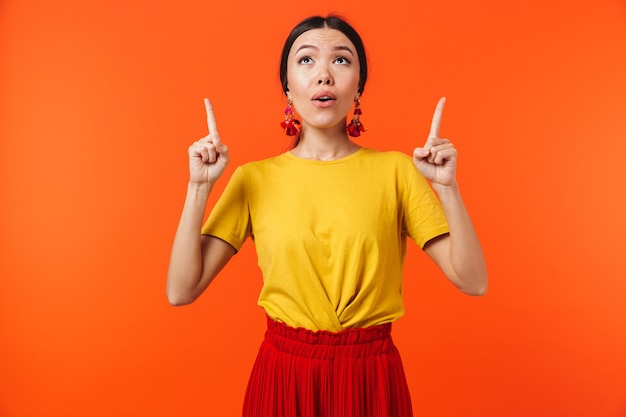 A beautiful excited shocked young woman posing isolated over orange wall pointing.