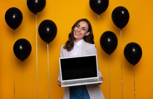 그녀는 검은 금요일 판매 시즌에 구매하는 동안 손에 노트북과 함께 아름 다운 흥분된 유행 성공적인 비즈니스 여자.