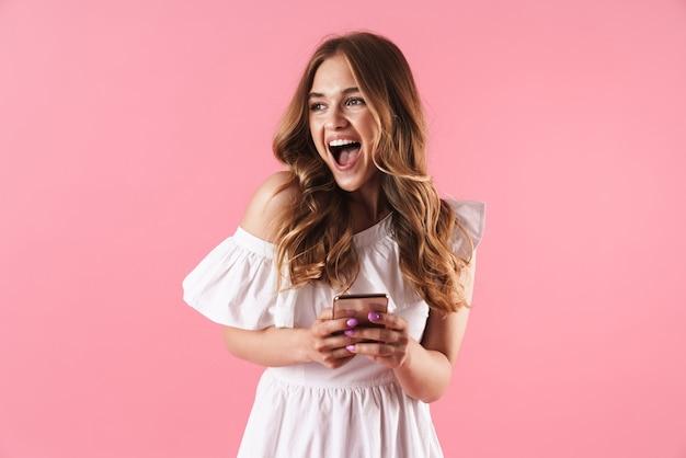 携帯電話を使用して、ピンクの壁の上に孤立して立っている夏のドレスを着て美しい興奮した若いブロンドの女の子