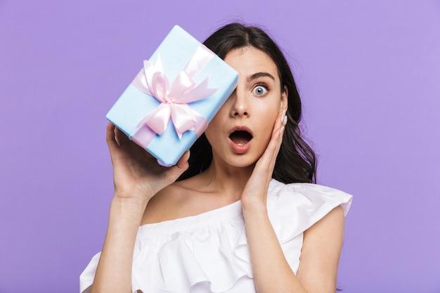 Красивая возбужденная молодая брюнетка женщина, стоящая изолированно над фиолетовой стеной, держа настоящую коробку