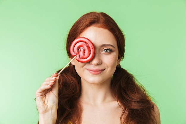 Beautiful excited young redhead girl posing isolated over green wall background with candy.