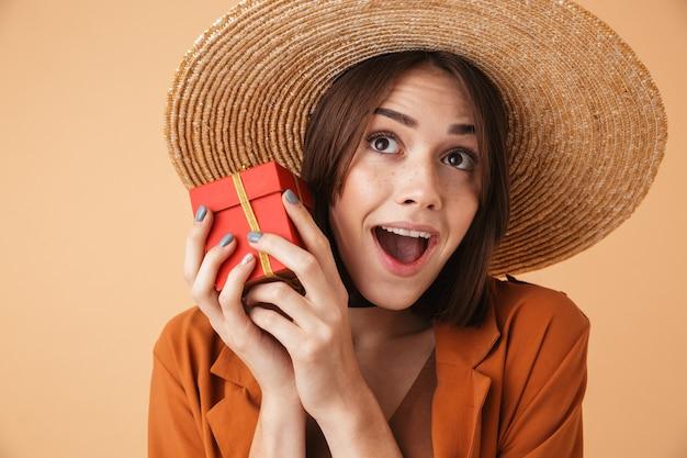 Красивая возбужденная молодая женщина в соломенной шляпе и летнем наряде, стоящая изолированно над бежевой стеной, держа в руках настоящую коробку