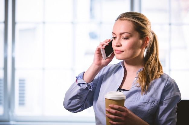 Beautiful executive listening to cellphone with coffee at creative office