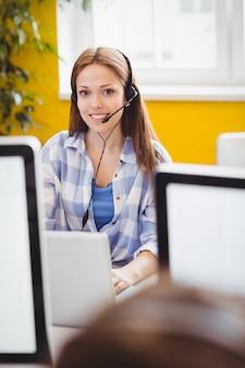 Beautiful executive with headphones using laptop at creative office