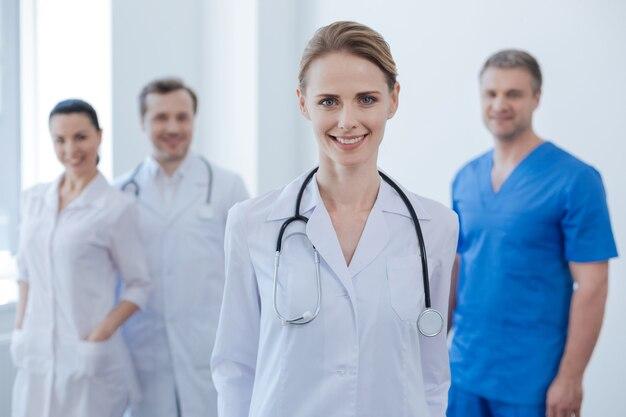 Красивая опытная зрелая медик стоит в клинике и улыбается, а ее коллеги выражают счастье позади