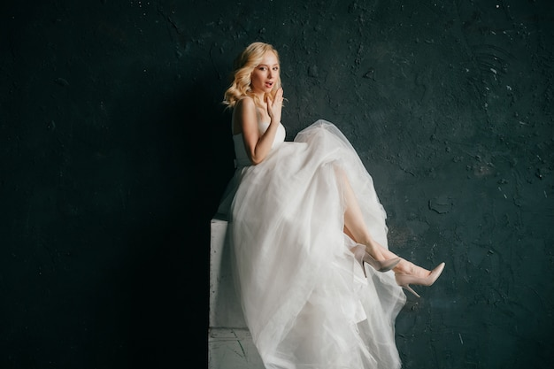 Beautiful expressive bride in white wedding dress pin up style portrait on black background.