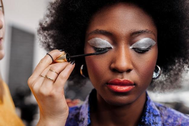 美しいまつげ。まつげにマスカラを塗りながら明るい唇が下を向いている黒髪の美しいモデル