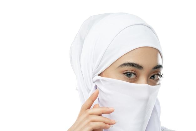 一枚の布で覆われた鼻と口の白いベールを持つ女性の美しい目