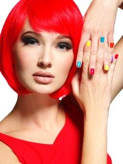 Bel viso di una ragazza con eleganti unghie multicolori