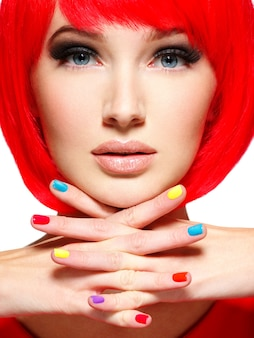 Beautiful face of a girl with stylish multicolor nails.