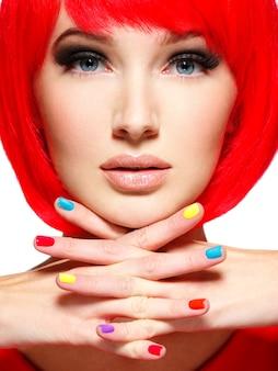スタイリッシュな多色の爪を持つ少女の美しい顔。