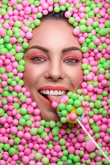さまざまなお菓子に囲まれたクリエイティブなメイクの若い女性の美しい顔
