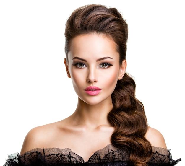 Красивое лицо молодой сексуальной женщины с длинными волосами, позирующей на белой стене
