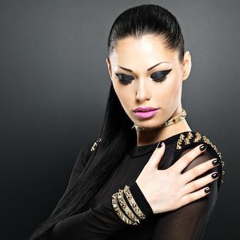 검은 손톱과 밝은 화장과 패션 여자의 아름 다운 얼굴. 목에 팔찌 가시와 섹시한 세련된 소녀