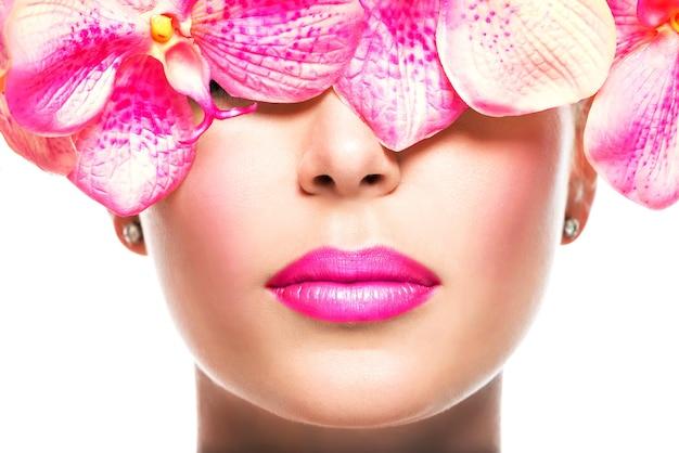 唇に明るい口紅とピンクの花を持つ女性の美しい顔-白で隔離