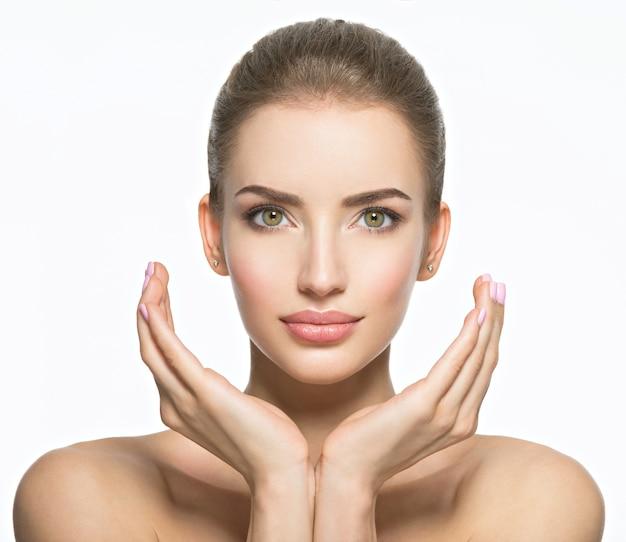 완벽 한 건강 피부-흰색 절연 젊은 백인 여자의 아름 다운 얼굴. 스킨 케어 개념. 여성 모델은 얼굴을 만집니다.