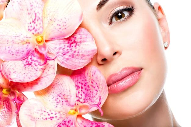 健康な肌とピンクの花を持つ若いきれいな女性の美しい顔-白で隔離