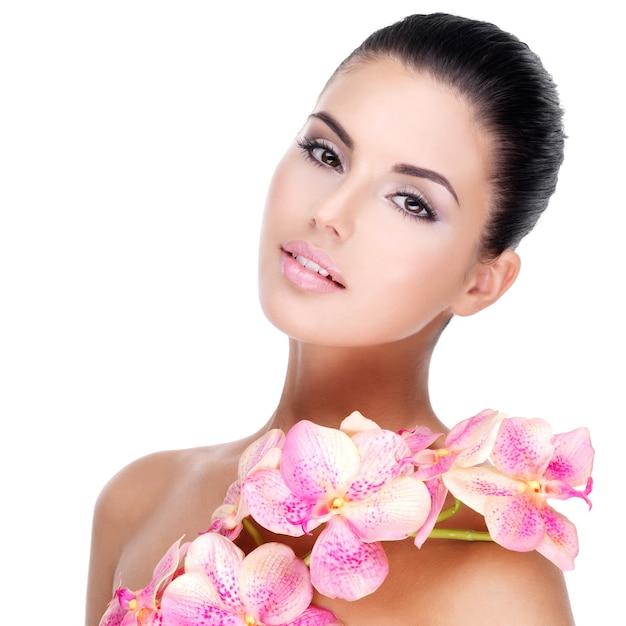 건강한 피부와 몸에 분홍색 꽃을 가진 젊은 예쁜 여자의 아름다운 얼굴-흰색에 고립