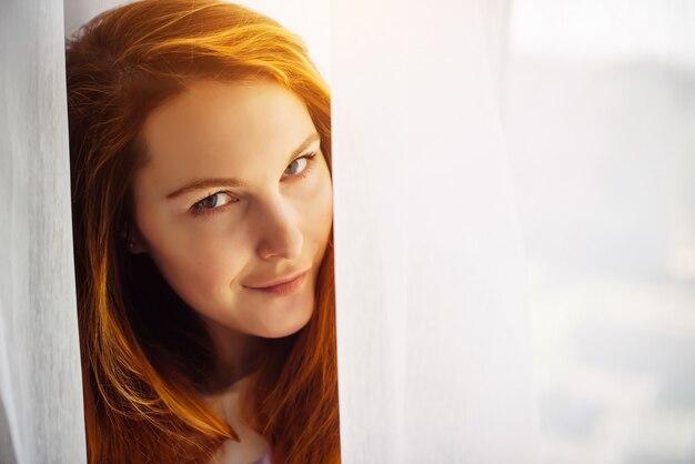 Красивое лицо молодой рыжеволосой женщины, крупным планом. брюнетка с гладкой кожей, глядя в камеру. изображение для рекламы косметики, ухода за кожей и волосами. размытый светлый фон, копией пространства.