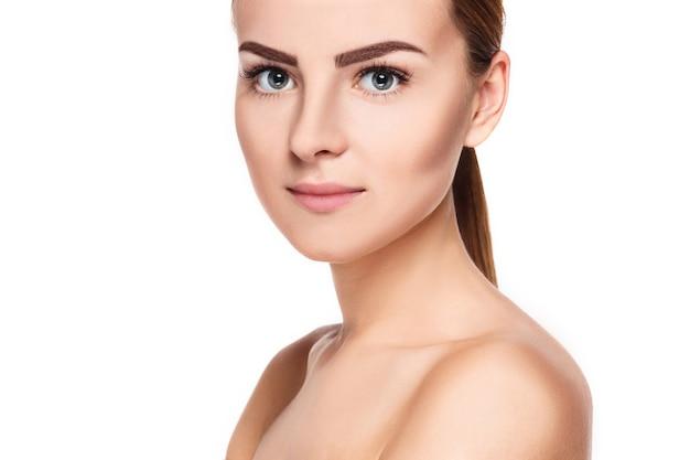 きれいな新鮮な肌を持つ若い女性の美しい顔は、白で隔離のクローズアップ。美しさの肖像画。完璧なフレッシュスキン。ピュアビューティーモデル。若者とスキンケアのコンセプト