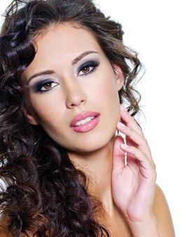 きれいな肌を持つ若い女性の美しい顔。長い巻き毛の女の子。ブライトアイメイク