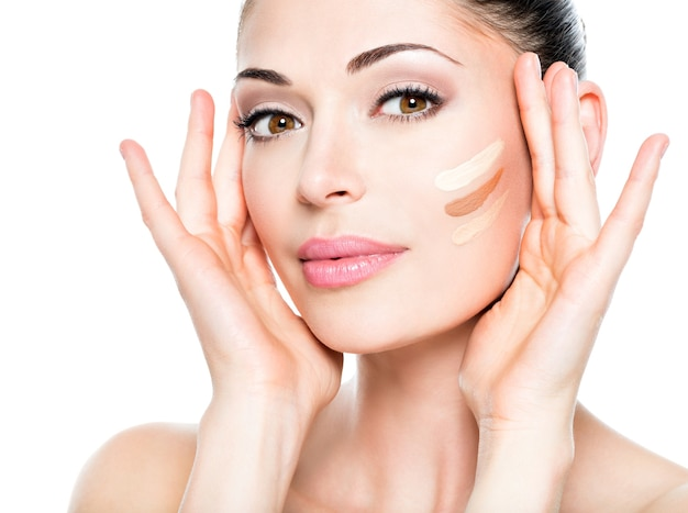 肌に化粧品のファンデーションを持つ若い女性の美しい顔。美容トリートメントのコンセプト