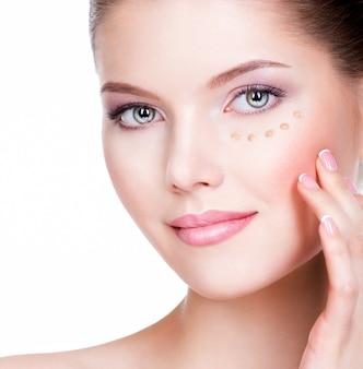 흰색 배경 위에 피부에 화장품 기초와 젊은 여자의 아름 다운 얼굴. 미용 치료 개념.