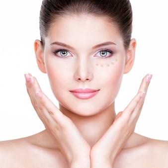 흰 벽에 피부에 화장품 기초와 젊은 여자의 아름 다운 얼굴. 미용 치료 개념.