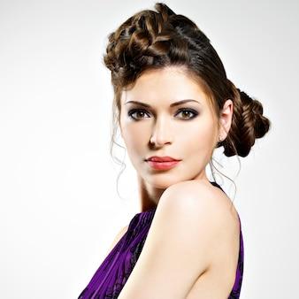 おさげ髪のデザイン、スタジオでポーズとスタイリッシュな髪型を持つ若い女性の美しい顔