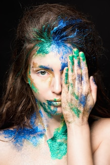 Beautiful face with colored paint on a black , beautiful girl, colorful makeup, fashionable woman,