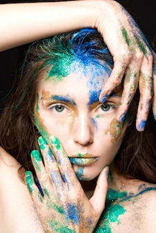 Beautiful face with colored paint on a black , beautiful girl,