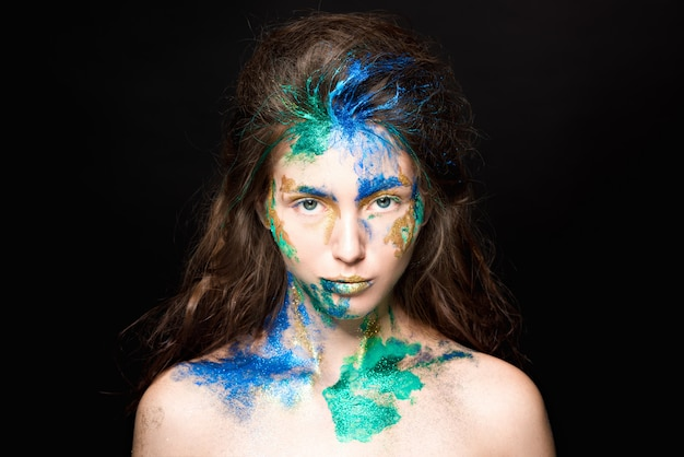 Beautiful face with colored paint on a black