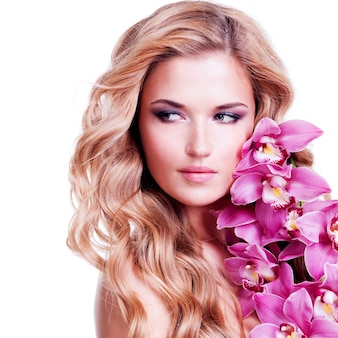 Beautiful face of young blond woman with healthy hairs and pink flowers near face - isolated on white.