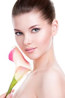 Bel viso di giovane donna graziosa con pelle sana e fiori rosa sul corpo - isolato su bianco.