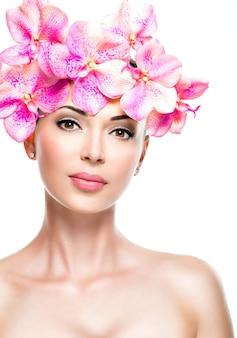 Bel viso di giovane donna graziosa con pelle sana e fiori rosa isolati su bianco