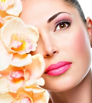 Bel viso di giovane donna graziosa con pelle sana e fiori bianchi isolati su bianco